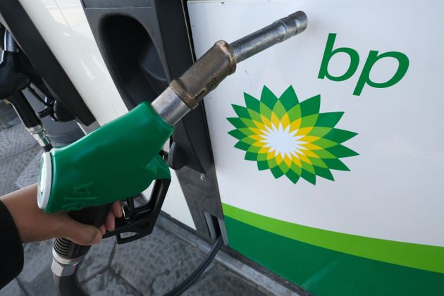 A man holds a gasoline hose beside a BP logo in the Netherlands on April 26, 2020.Major companies...