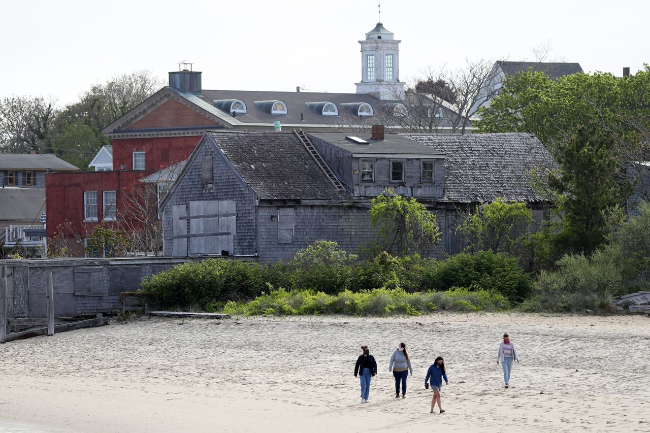 People walk on the beach at Provincetown Harbor on May 25. The country's unofficial LGBTQ summer playground faces a greater challenge this year because of the coronavirus.