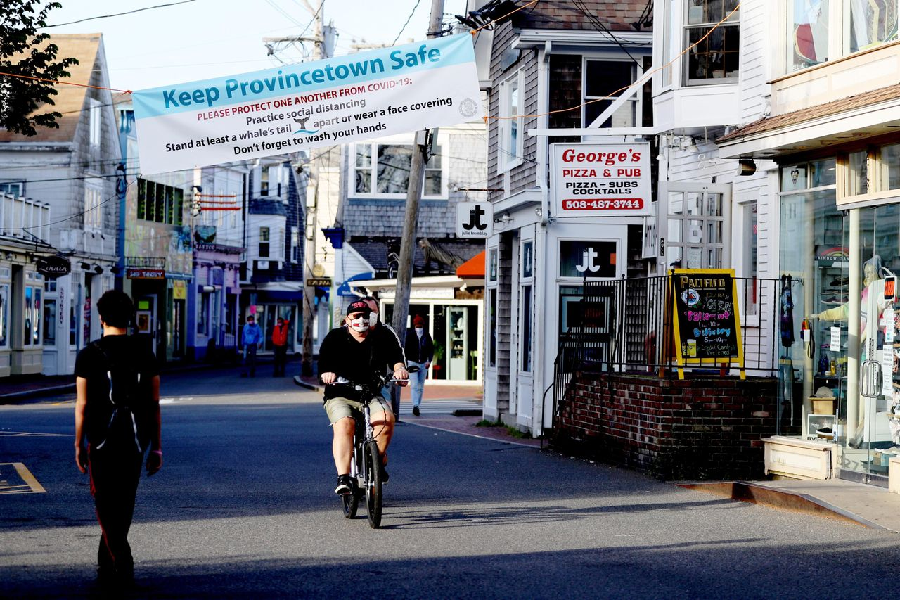 A biker rides down Commercial Street on May 25, 2020, in Provincetown. Massachusetts has now begun phase two of reopening after the coronavirus shutdown, with restaurants, lodging and retail allowed to operate with safety modifications.