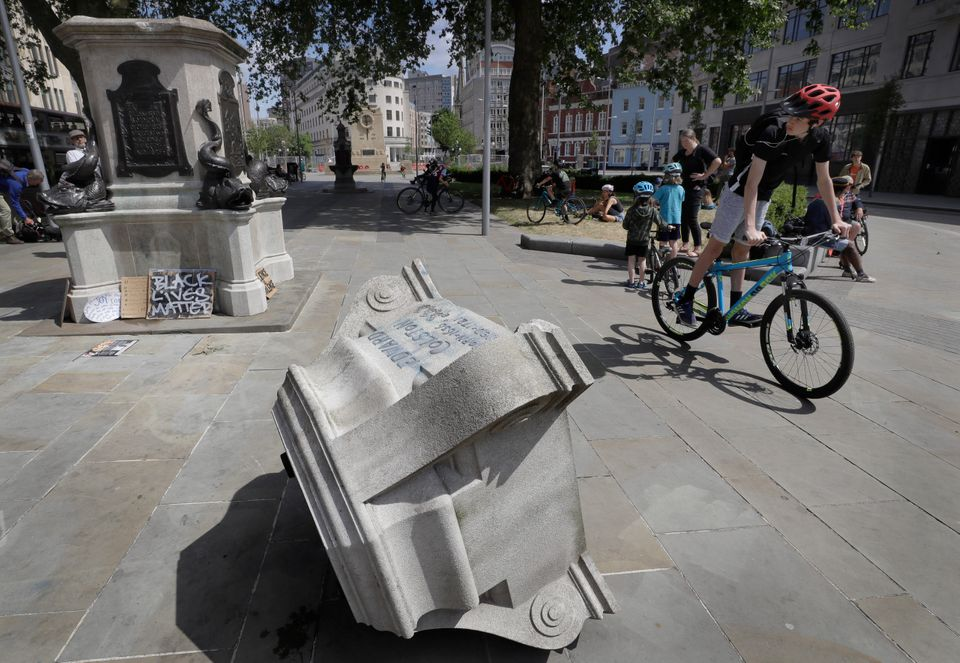 Passers-by look at the pedestal of the toppled statue of Edward Colston on