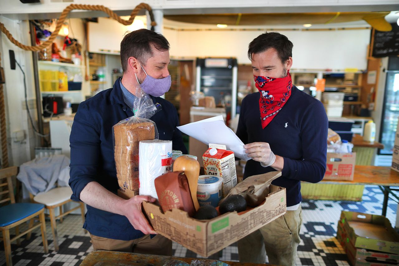 Rob Anderson (left), co-owner of the Canteen, and his partner and co-owner Loïc Rossignon make up a grocery order for delivery inside their Provincetown restaurant on May 13.