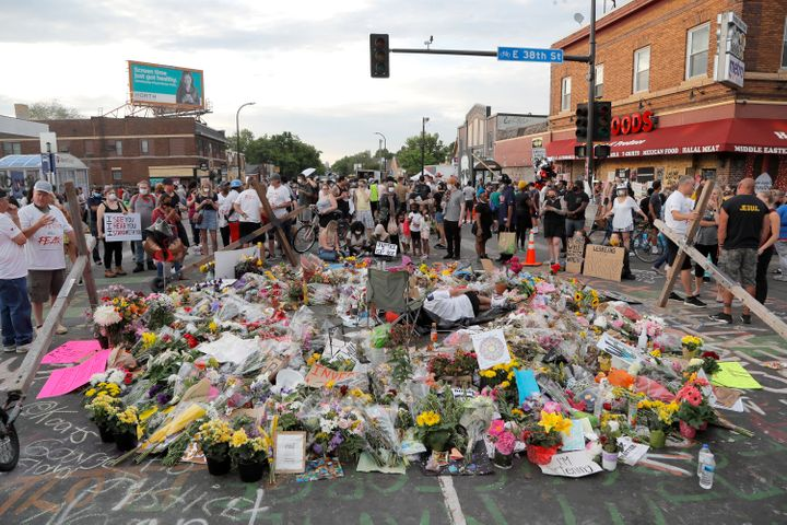 People gather around a makeshift memorial for George Floyd, Wednesday, June 3, 2020, in Minneapolis. (AP Photo/Julio Cortez)