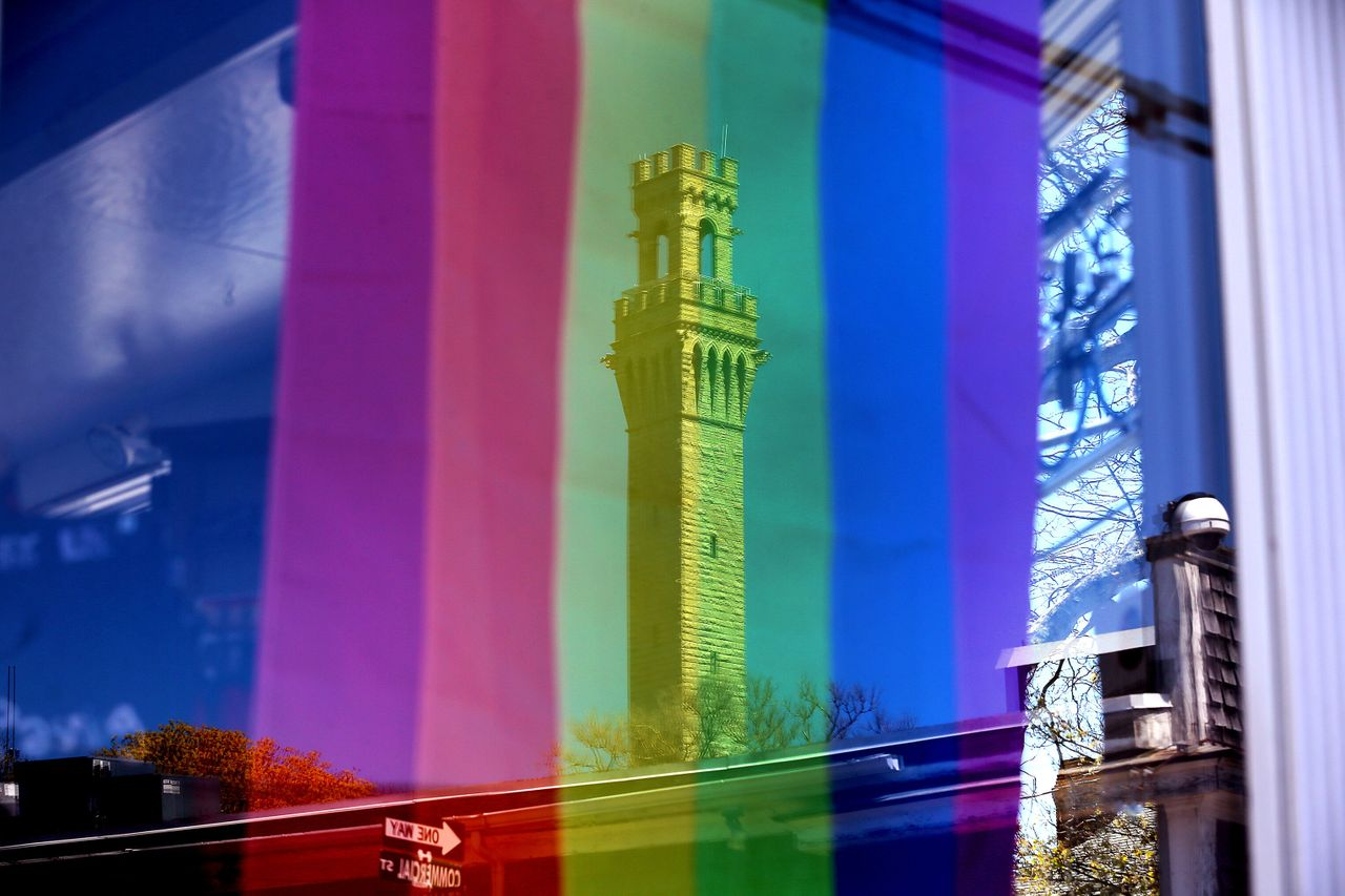 A rainbow flag hangs in a Commercial Street business window that reflects the Pilgrim Monument in Provincetown on May 13.