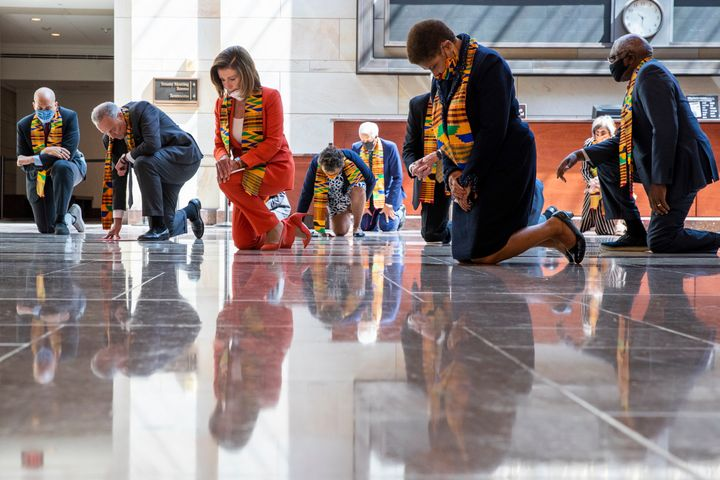 House Speaker Nancy Pelosi of Calif., center, and other members of Congress, kneel and observe a moment of silence at the Cap