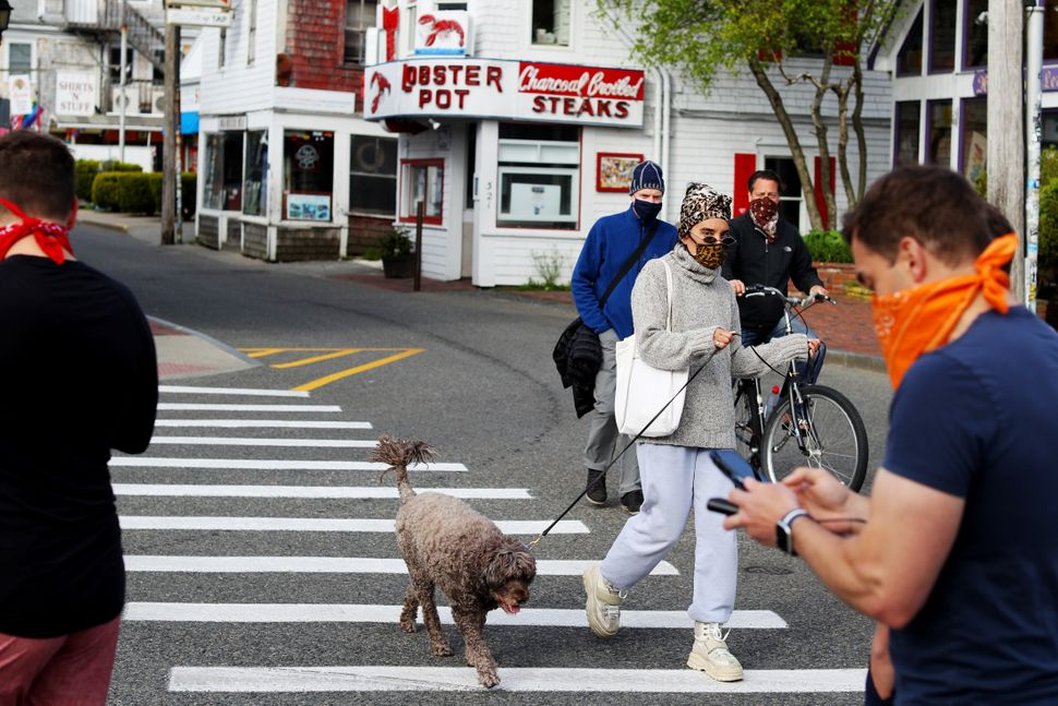 People wearing face masks walk down Commercial Street on May 25.