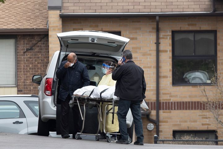 A body is removed from Orchard Villa home in Pickering, Ont. on April 26, 2020.