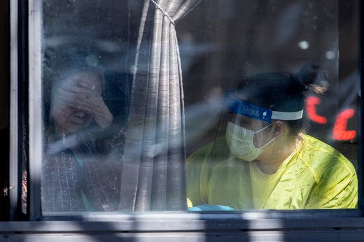 A resident talks to a staff member after receiving absolution from a priest at Orchard Villa home in Pickering, Ont. on April 25, 2020.