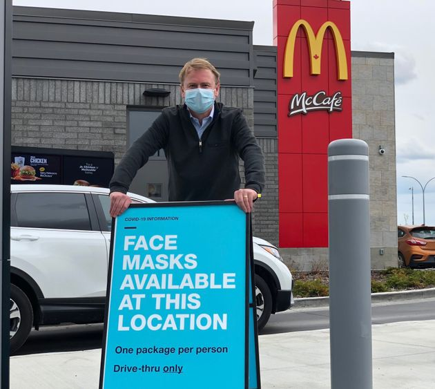 Alberta Health Minister Tyler Shandro poses with a sign outside of an Alberta McDonald's