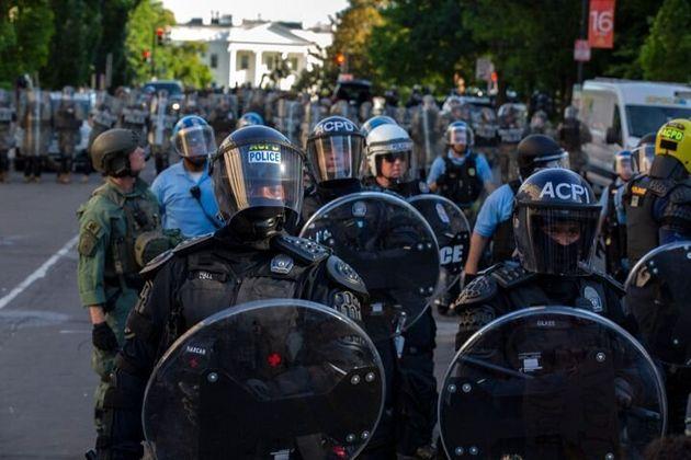 暴徒鎮圧用の装備をして、デモに備える警察官たち。後ろにホワイトハウスが見える