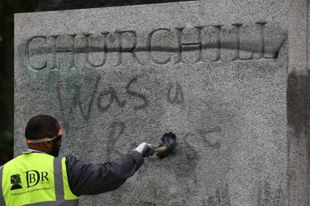 A worker cleans graffiti from the plinth of the statue of Sir Winston Churchill at Parliament Square...