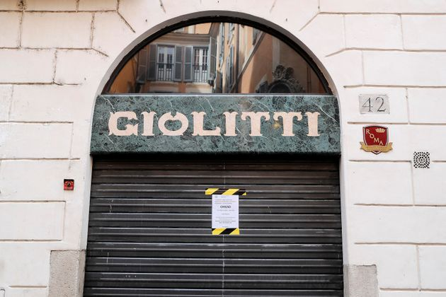 Daily life during the coronavirus emergency in the center of Rome, a closing sign on the shutter of Giolitti...
