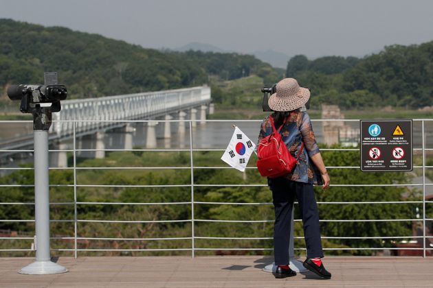 A visitor carrying a South Korean flag uses binoculars to view the northern side at the Imjingak Pavilion...