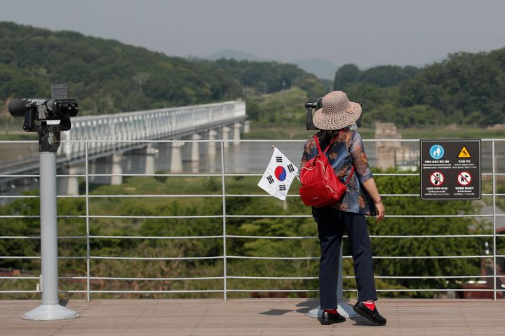 A visitor carrying a South Korean flag uses binoculars to view the northern side at the Imjingak Pavilion in Paju, South Kore