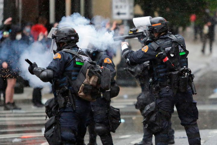 """Washington State Police uses tear gas to disperse a crowd during a demonstration protesting the death of George Floyd, a black man who died May 25 in the custody of Minneapolis Police, turned destructive in Seattle, Washington on May 30, 2020. - Clashes broke out and major cities imposed curfews as America began another night of unrest Saturday with angry demonstrators ignoring warnings from President Donald Trump that his government would stop violent protests over police brutality """"cold."""" (Photo by Jason Redmond / AFP) (Photo by JASON REDMOND/AFP via Getty Images)"""