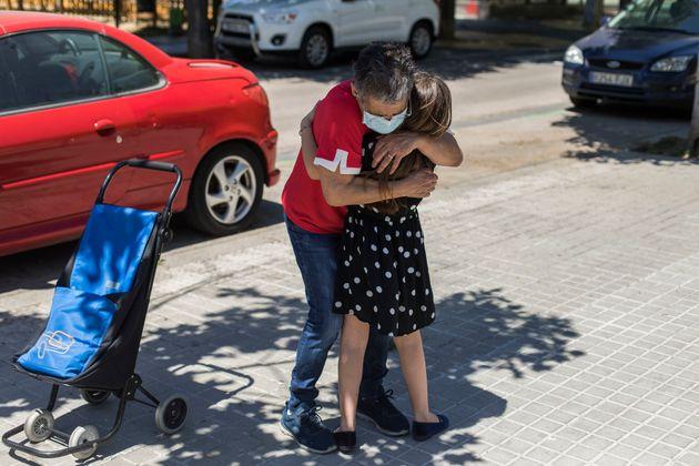 Una abuela abraza a su nieta por primera vez desde que se decretó el confinamiento por el coronavirus....