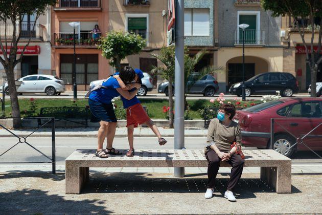 Una mujer abraza a un niño en el barrio de Ayerbe, en Huesca, el 23 de