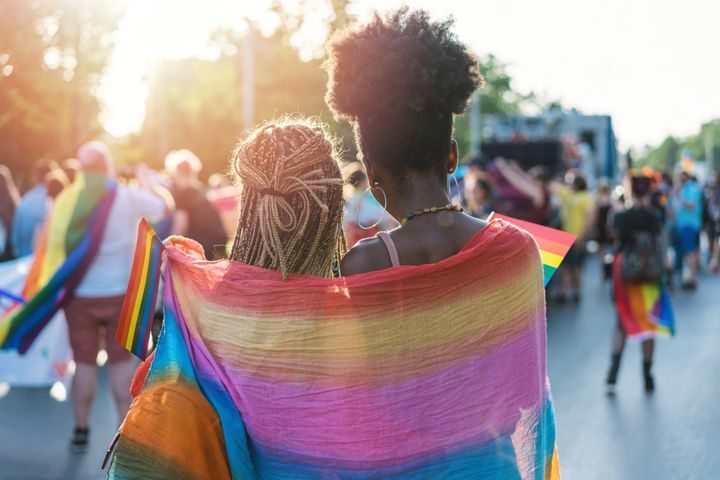 Rear view image of young couple walking with the pride event, hugging and waving pride flags