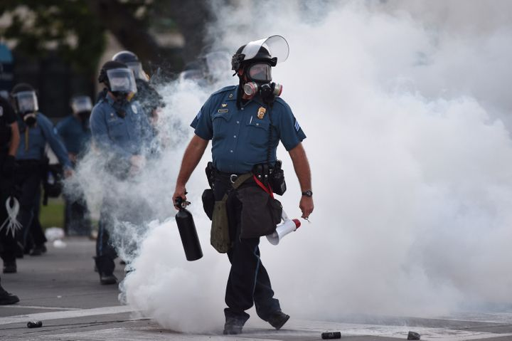 Law enforcement officers stand guard after tear gas is deployed near 47th and Main streets in Kansas City, Missouri, on May 3