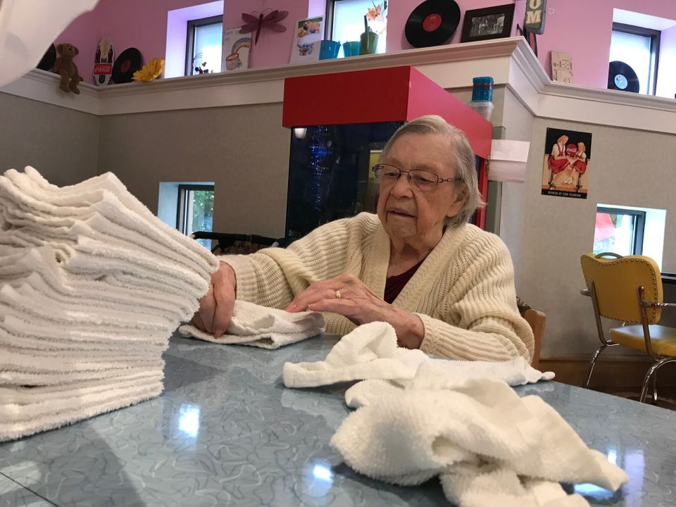 A resident folds towels in an undated photo at Sunnyside Home in Kitchener, Ont., where staff are working...