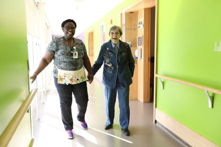 Malton Village resident Inga Cherry walks through the hallway with Geva Lindsay, a personal support worker, at the Mississauga, Ont. home.