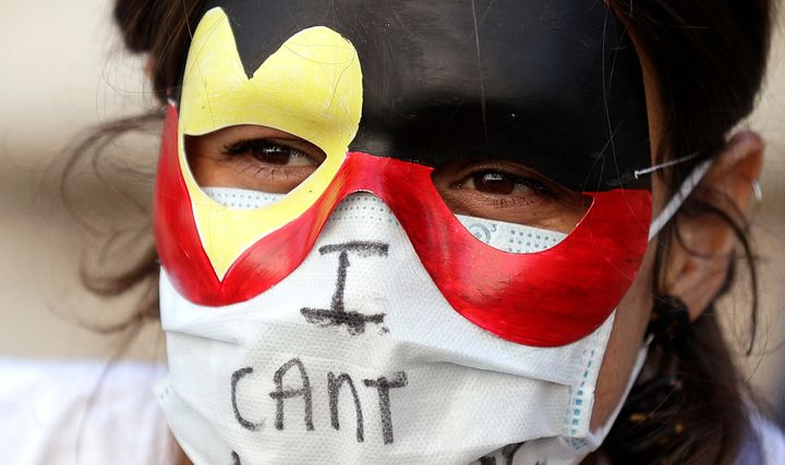 A protester wears a mask as thousands gather at Town Hall in Sydney, Saturday, June 6, 2020, to support the cause of U.S. protests over the death of George Floyd. Black Lives Matter protests across Australia proceeded mostly peacefully as thousands of demonstrators in state capitals honored the memory of Floyd and protested the deaths of indigenous Australians in custody. (AP Photo/Rick Rycroft)