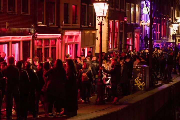 Tourists pack Amsterdam's red-light district. In January, the city banned tours past the windows where sex workers pose to re