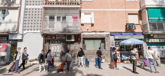 Un grupo de vecinos del barrio de Aluche hace cola para recibir alimentos durante la pandemia del