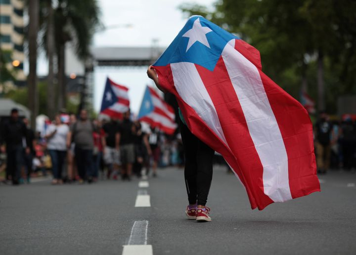 A person carries a Puerto Rican national flag during a protest against the government's austerity measures in 2017. &nbs