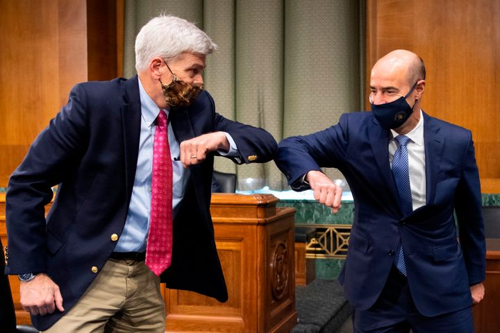 Sen. Bill Cassidy (R-La.), left, elbow-bumps Labor Secretary Eugene Scalia before the start of a Senate Finance Committee hea