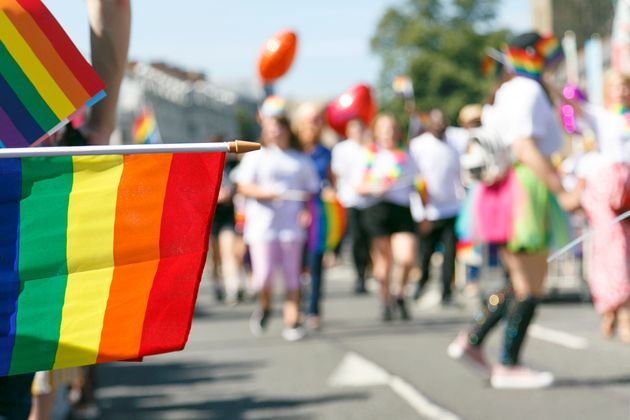 Participants and supporters of a Gay Pride Parade in Cardiff. Selective focus on a rainbow flag with...