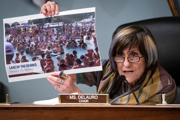 Rep. Rosa DeLauro (D-Conn.) holds up a photograph of partygoers in Lake of the Ozarks, Missouri, celebrating Memorial Day wee