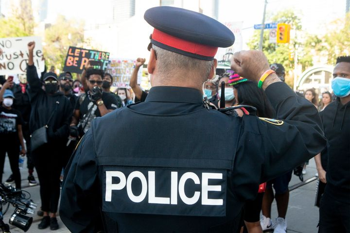A police officer throws up a fist as protesters march in an anti-racism rally in Toronto on June 6, 2020.