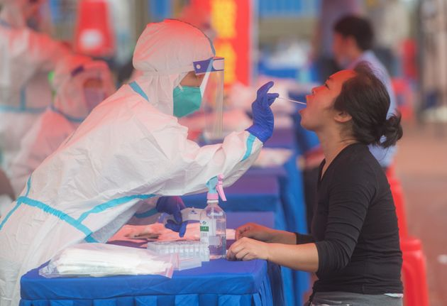 A resident takes nucleic acid test at a testing site in Dongxihu District in Wuhan, central China's Hubei...