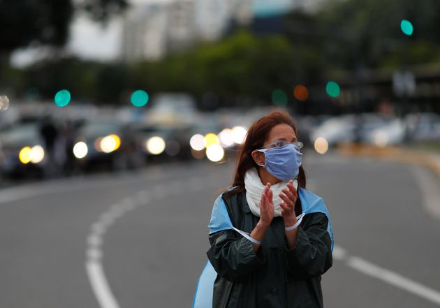 An anti-quarantine demonstrator applauds, during a protest against the quarantine measures in the city...