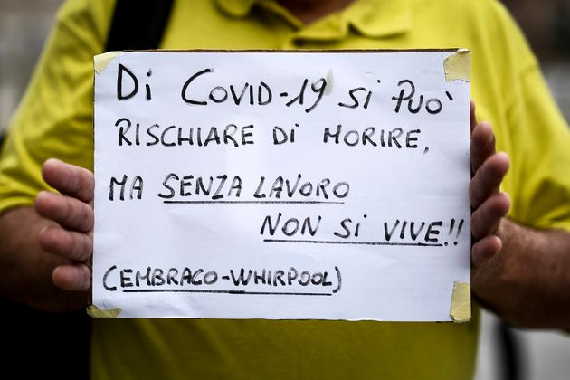 PIAZZA CASTELLO, TURIN, ITALY - 2020/06/04: A protester holds a placard reading 'Because of Covid-19...