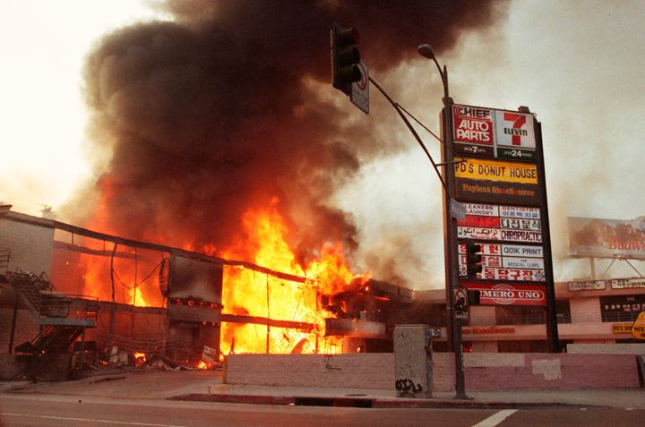 A corner shopping center in Koreatown is left burning out of control in Los Angeles on the third day of the 1992 Los Angeles