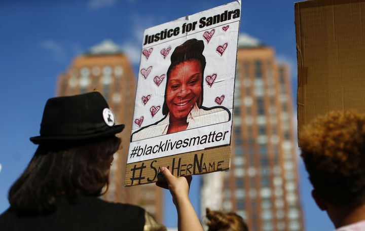 A woman holds a poster bearing the portrait of Sandra Bland in New York on Aug. 9, 2015.