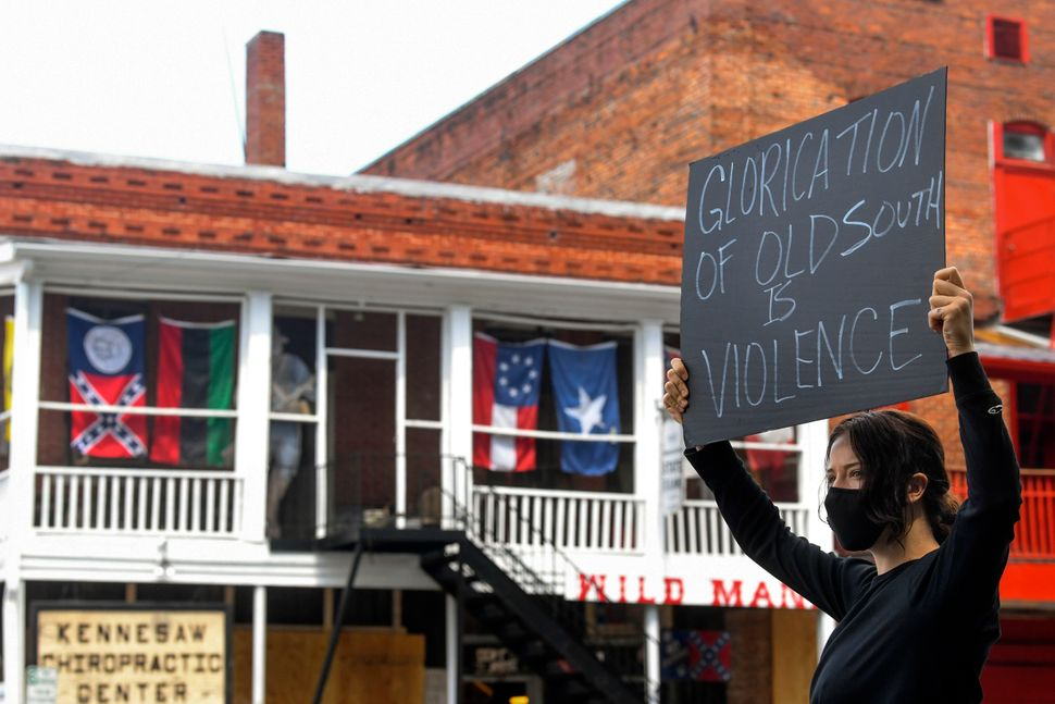 Chelsea Shag holds up a sign as demonstrators protest June 5 across the street from a Confederate memorabilia store in Kennes
