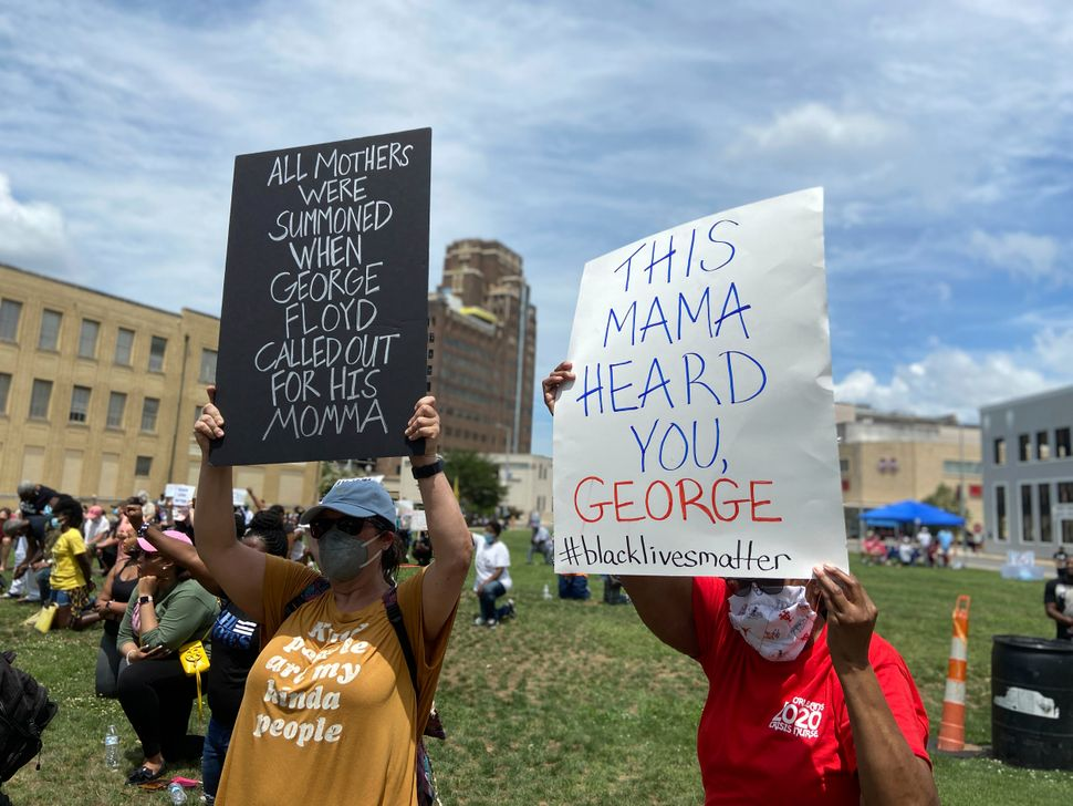 """Lee Cottrill and Cheryl Cockrell hold up signs during the """"Breathe Through Me Peace Rally"""" in Meridian, Mississippi, on June"""