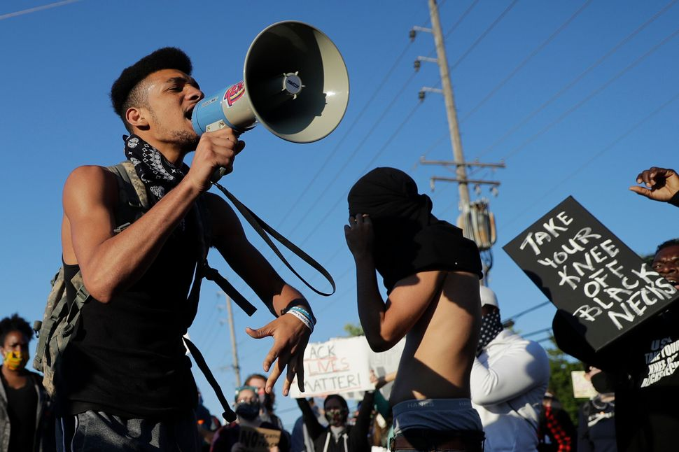 A protester uses a megaphone June 10 while blocking a street outside the police station in Florissant, Missouri. Several hund