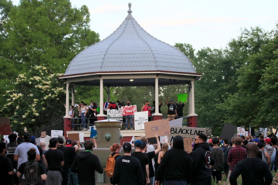 Protesters hold signs at a rally at a park in Lawrence, Kansas, on May 31 over the death of George Floyd and other Black vict