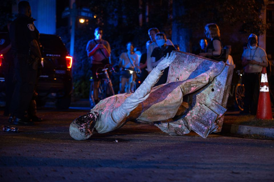 A statue of Confederacy President Jefferson Davis lies on the street after protesters pulled it down...