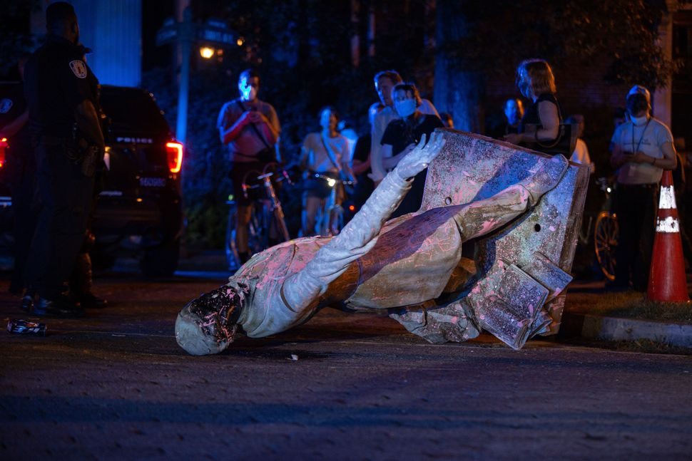 A statue of Confederacy President Jefferson Davis lies on the street after protesters pulled it down in Richmond, Virginia, o