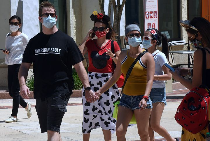 People flocked to Disney Springs ― the retail, dining and entertainment complex at Walt Disney World ― on the day it began its phased reopening in May. Masks and temperature checks are required there as well.