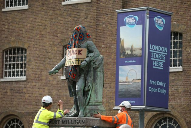 Workers prepare to take down a statue of slave owner Robert Milligan in London on Tuesday after a protest...