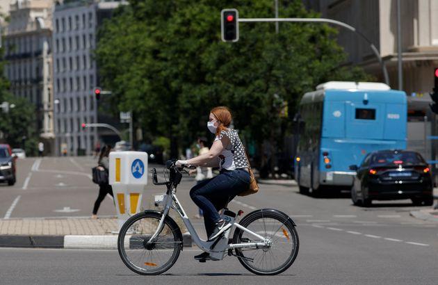 Una señora utiliza una bicicleta de BiciMad durante el primer día de uso de las