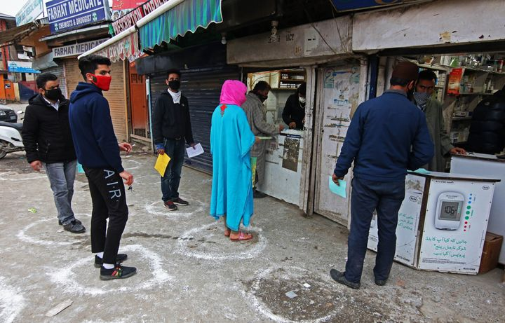 People maintain social distancing, due to the coronavirus (Covid-19) pandemic as they wait for their turn to collect medicines from a pharmacy in Srinagar, Kashmir, India on March 26, 2020.