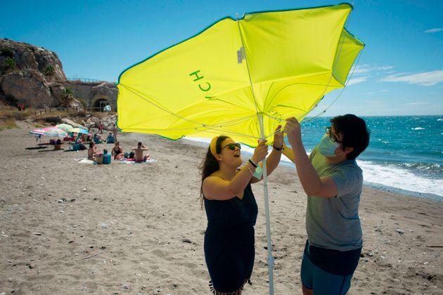 Una pareja coloca una sombrilla en la playa de La Arana, en