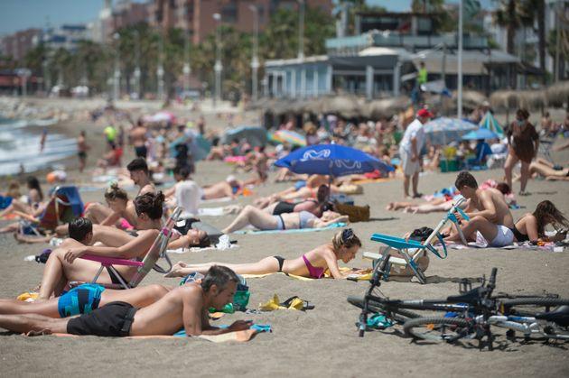 Varias personas toman el sol en la playa de La Misericordia, en