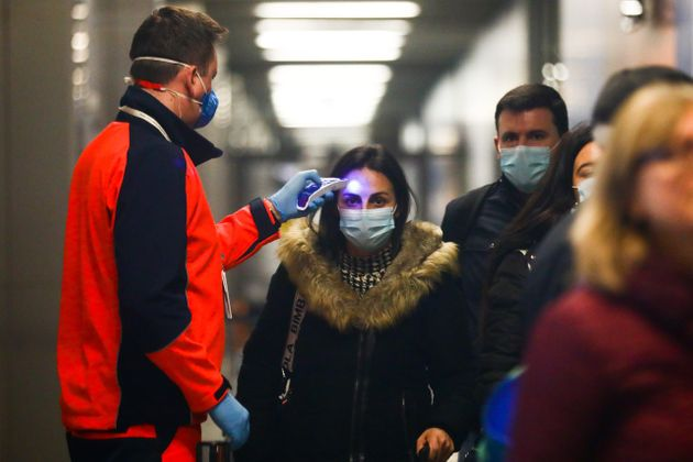 Health personnel monitors body temperature of passengers who arrived in a flight from Milano, Italy to...